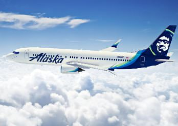 Picture of Alaska airlines jet flying above the clouds.